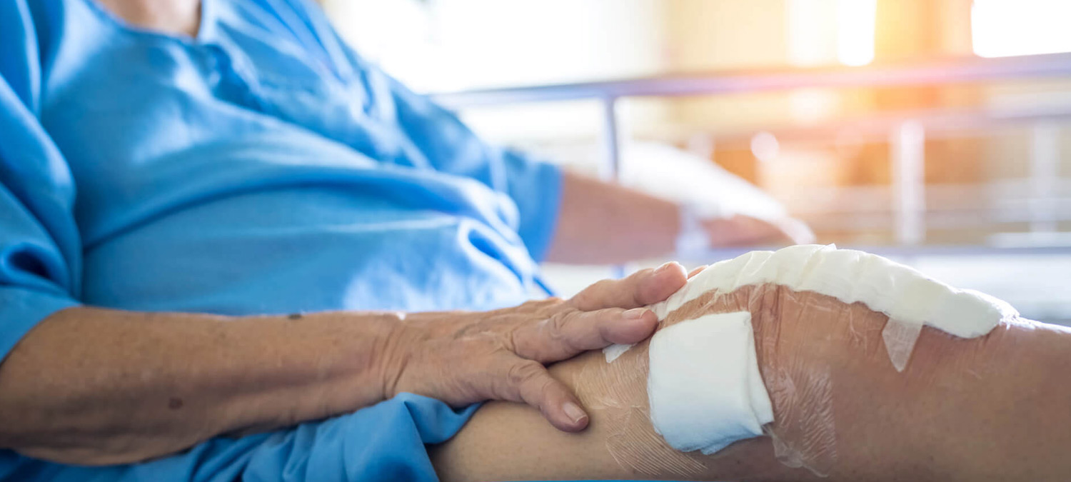 Closeup of a person holding their leg, which is covered in gauze and bandages.