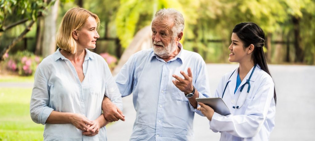 A woman walks arm in arm with an elderly man as a woman in a white lab coat wearing a stethoscope talks to them.