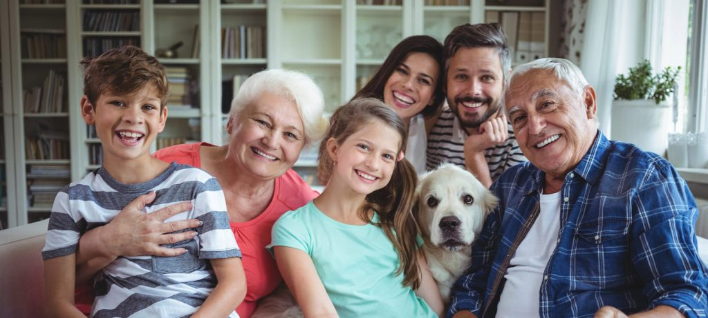 A family including children, parents, grandparents, and a dog smiling at the camera.