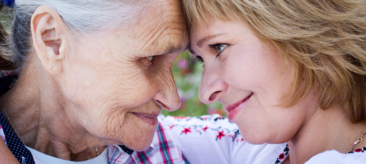 An elderly woman and a younger woman smiling while pressing their foreheads together in an embrace.