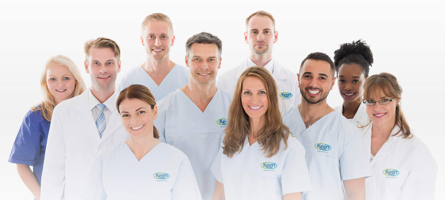 A group of people in white Keen Home Care scrubs and lab coats smiling at the camera.