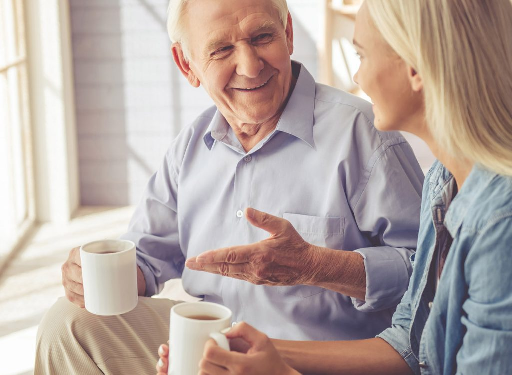 A younger woman talking to an elderly man while smiling and holding coffee cups.