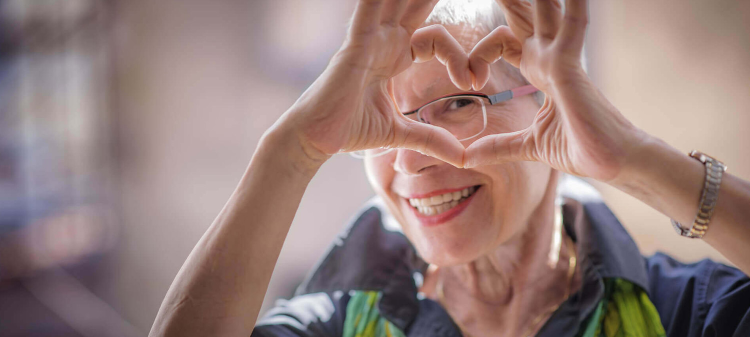 A woman making a heart shape with her thumbs and pointer fingers.