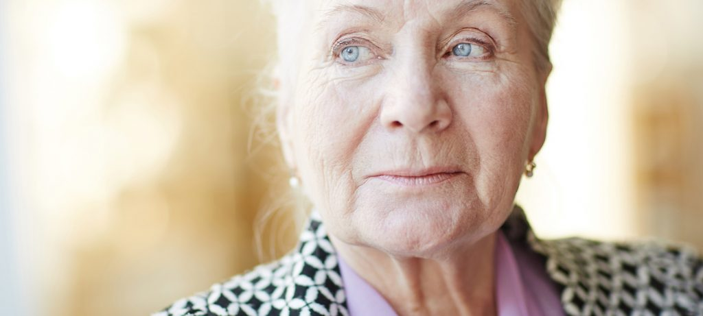 Closeup of an elderly woman looking off into the distance.