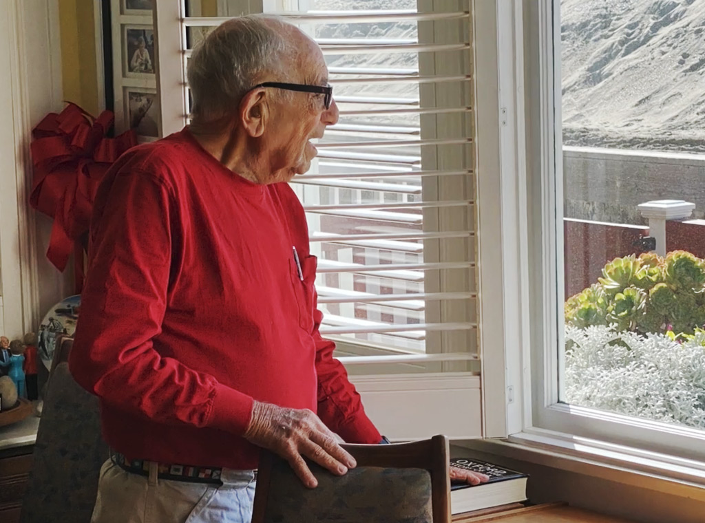 An elderly man in a red shirt standing next to a window while staring outside.