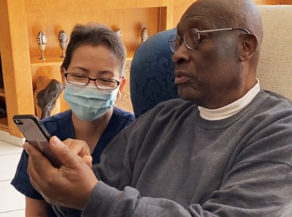An elderly man shows something on his cellphone to a woman wearing scrubs, glasses, and a face mask.