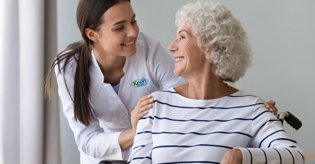 A woman in a white lab coat smiling and resting her hands on an elderly woman's shoulders.