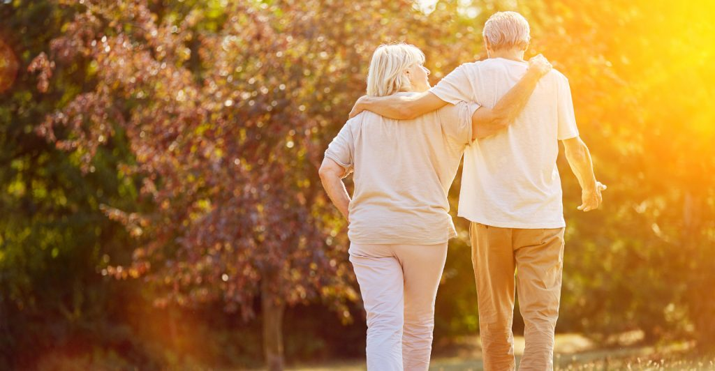 Elderly man and woman walking arm in arm away from the camera towards a ray of sunlight.